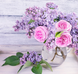 Bouquet of lilac flowers and roses in glass bottle