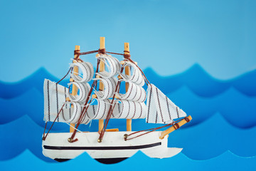 White Ship on blue wave with paper. Travel and adventure concept