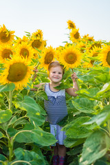 Little girl in striped dress and rubber boots  holds in hands two sunflowers. Sunny summer day in field of sunflowers.