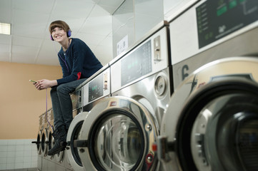 Germany, Bavaria, Young woman listening music on top of washing machine, smiling