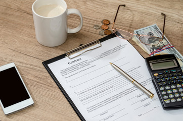 coffee and contract, money, mobile phone on desk