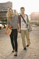 Germany, Bavaria, Portrait of teenage couple coming from school, smiling