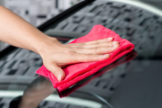 Car polishing series : Hand of worker using red towel wiping windshield