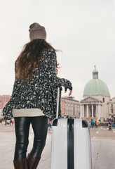 Seen from behind young woman with big luggage bag in Venice