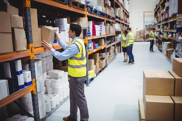 Smiling warehouse worker taking package in the shelf