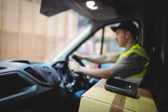 Delivery driver driving van with parcels on seat