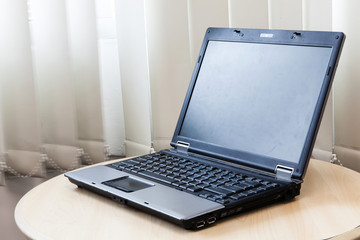 Laptop with blank screen on wooden table.