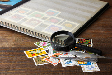 open the album with a very large and expensive collection of stamps on wooden brown table near to a bunch of other more valuable stamps near magnifier with  tweezers