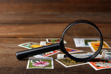 a small pile of expensive and collectible stamps with a magnifying glass on wooden brown table