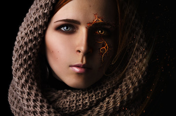 Fantasy processing portrait of a young girl with a burning pattern on the face in a scarf on a black background