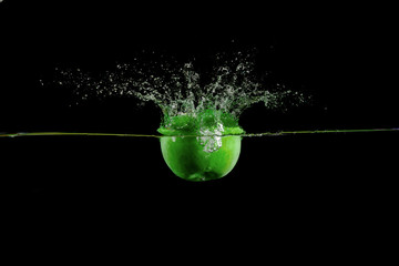 green apple fell into the water and climb up many splashes