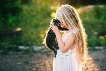Baby girl holding hands a kitten in the light of sunset, pet, friend,