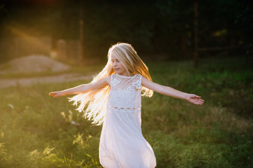 Portrait of a baby girl spinning in a field in sunset light, life style
