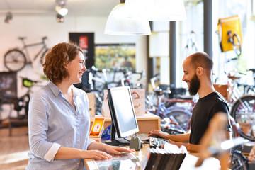 Obraz Lifestyle Shopping - junge Frau kauft in einem Fahrradladen ein, Beratung durch Verkäufer - fototapety do salonu