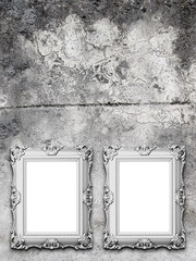 Close-up of two silver baroque picture frames on stained concrete wall background