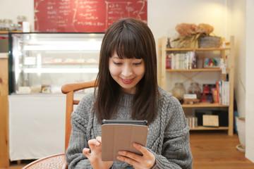 カフェでタブレット端末を使う女性
