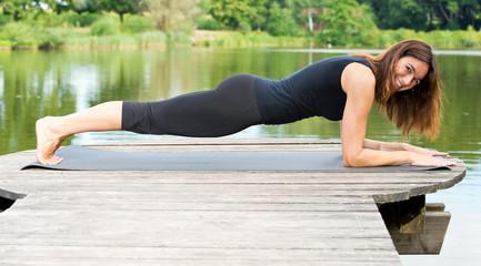 Frau im Unterarmstütz / Plank, draußen am idyllischen Weiher
