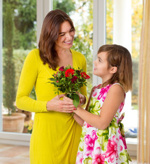 Tochter / Kind überreicht Mama Blumen zu Muttertag