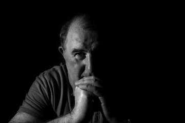 Dark black and white image of a mature man resting his head on his hands looking into the camera.