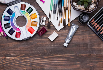 Artist supplies on the wooden background