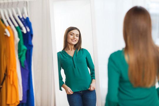 happy woman posing at mirror in home wardrobe