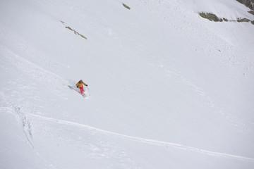 freeride skier skiing in deep powder snow