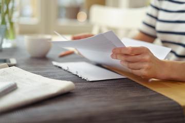frau sitzt am küchentisch und liest einen brief