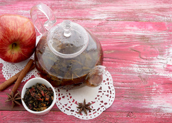 Ripe apple, cinnamon and fruit drink in glass teapot on wooden background