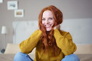 lachende frau mit langen roten haaren zu hause