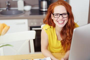 frau sitzt in der küche und arbeitet am computer
