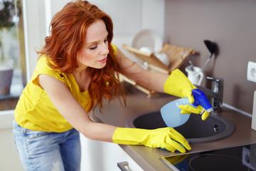 frau reinigt den herd in der küche