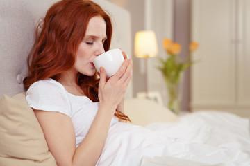 frau genießt eine tasse tee im bett