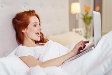 frau liegt im bett und schaut lachend auf ihr laptop