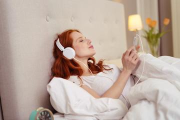 frau liegt mit kopfhörern im bett und hört musik