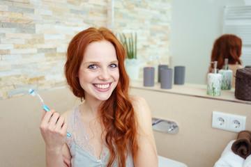 frau im bad mit zahnbürste und strahlendem lächeln
