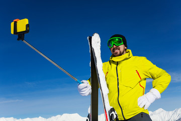 Skier man taking selfie with stick,over sky