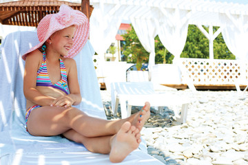 Luxury resort little girl relaxing . Caucasian cute child lying