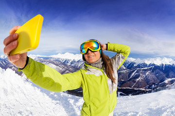 Woman take selfie over mountain and ski tracks