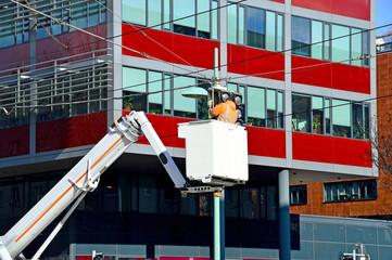 Arbeiter auf einer Gelenkteleskopbühne beim Reparieren einer Verkehrsampel
