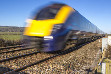 Close up of train speeding through English countryside with motion blur