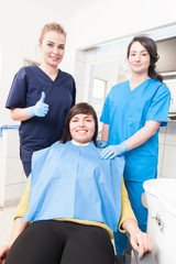 Cheerful woman dentist thumbup while patient and assistant are s