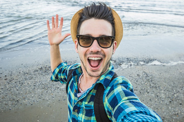 Handsome caucasian man take a selfie at the beach - people, lifestyle, nature and technology concept