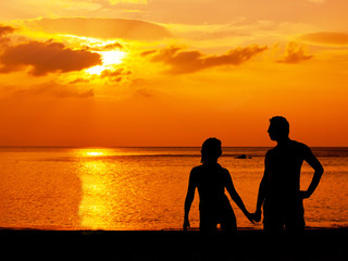 Love feeling background. Silhouette of couple near beautiful golden sunset sky and ocean background on the beach