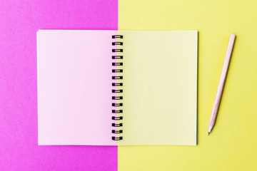 Open notebook and pencil on multicolor background