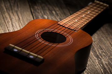 Close up of ukulele on wooden background.