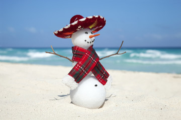 Miniature snowman wearing Mexican sombrero and scarf on the beac
