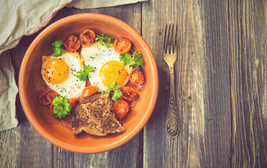 Fried eggs with cherry tomatoes and parsley in clay dish