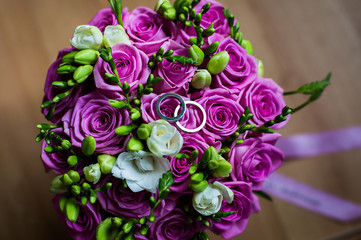 wedding flowers, wedding bands, wedding rings lie on a wedding bouquet of beautiful pink roses and white flowers,bouquet of roses