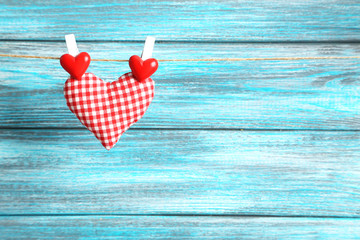 Love heart hanging on rope on a blue wooden background