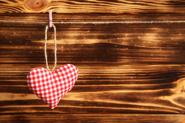 Love heart hanging on rope on a brown wooden background